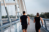 Young couple doing morning workout outdoors. Young man and woman running on bridge.
