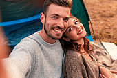Portrait of happy young couple sitting by tent at campsite.