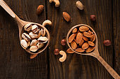 Nuts in wooden spoons on a dark wooden table.