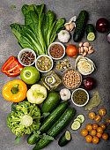 collection of different vegetables and spices, ingredients for preparing a healthy vegetarian food. Top view on a gray background. Diet concept