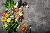 set of different vegetables and spices, ingredients for preparing a healthy vegetarian food. Top view on a gray background with space for text.