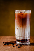 Iced coffee with ice. Frappe, frappuccino with cream and cinnamon on a wooden table. copy space