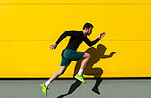 Portrait of male athlete running isolated on yellow wall.
