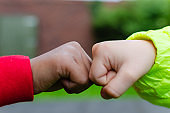 Two children of different races greeting each other with fist bump. Photo shows friendship, support, equality and diversity. One Caucasian (white complexion) the other is dark (black).