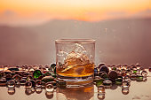 A Glass Of whiskey with ice and gold sunlight. Outdoor shot of whiskey with splash on sunset background.