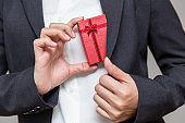 Businessman pulls a gift box out of his suit for giving their company worker for year end big bonus.