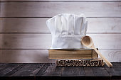 Chef hat, old books and wooden spoon on the kitchen table.