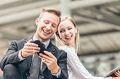 Couples friend, business men and women are interested in looking at mobile screens happily smile and laugh.
