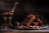 Pieces chocolate Brownie cake, chocolate and cocoa beans on a dark wooden background
