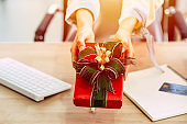 Business people closeup hand giving present gift box in office party celebration event.