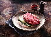 Raw Beef Steak Ribeye with rosemary and pepper