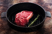 Raw Beef Steak Ribeye with rosemary in a cast-iron frying pan