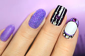 Multi-colored manicure with white and lilac varnish on various forms of nails