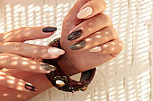 Multicolored brown milk manicure on oval long nails and a bracelet on his hand
