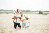 An Happy family of four having fun in the wheat field on sunny summer day.