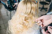 Back view of hairdresser working with long blonde hair of her customer in barber shop.