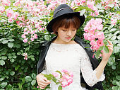 young brunette woman in white lace dress and hat posing in rose garden. Outdoor fashion portrait of glamour Chinese stylish girl. Emotions, people, beauty and lifestyle concept.
