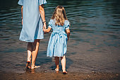 Young woman and her daughter barefoot walk in the water on a river. Back view. Closeup