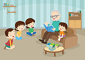 grandparents with grandchildrens reading on sofa