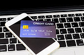 credit card put on mobile phone and laptop keyboard