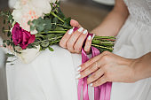 wedding flowers in hands of young bride sitting alone in home interior