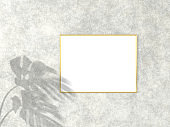 3x4 horizontal Gold frame for photo or picture mockup on concrete background with shadow of monstera leaves. 3D rendering.