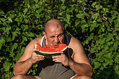 Brutal man enjoying sweet red watermelon. 35-years old male model sitting on nature green background and eating fresh fruit. Happy eating person.