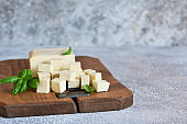 Soy cheese - classic tofu cheese on a wooden board on the kitchen table.