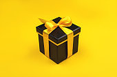 One black gift box on yellow background.