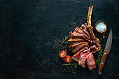 Grilled dry aged tomahawk steak sliced as close-up