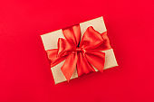Cardboard gift box with bow on red background.
