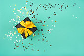 Gift box with yellow bow on green background with sparkling confetti.