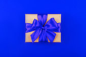 Cardboard gift box with bow on blue background.