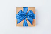 Cardboard gift box with blue bow on white background.