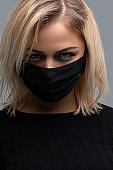 Woman wearing the black face mask. Air pollution concept.