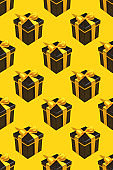 Pattern with lot of black gift boxes on yellow background.