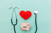 Medicine doctor equipment stethoscope or phonendoscope piggy bank and red heart isolated on trendy pastel blue background
