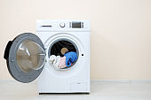 washing machine with laundry in drum near beige wall