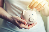 Woman hands holding pink piggy bank and putting money Euro coin