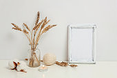 Vertical frame mockup with wild rye bouquet in glass vase near white wall