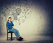 Woman seated on a chair keeps hand under chin thoughtful looking away, find solutions to solve problems. Different imagination, alternative ideas. Gear brain as thoughts. Mental development concept.