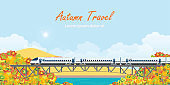 Speed train on railway bridge on colorful autumn trees.
