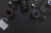 Photographer workplace with dslr camera system, camera cleaning kit, lens and camera accessory on dark black table background