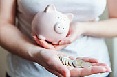 Woman hands holding pink piggy bank and euro coins