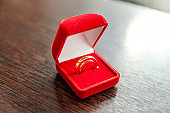 Two beautiful wedding rings on red jewelry box on light background