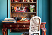 Luxury classic interior of home library. Sitting room with bookshelf, books, table and chair