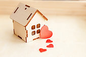 Miniature toy model house with red heart on wooden backdrop. Eco Village abstract environmental background. Real estate mortgage property insurance sweet dream home ecology concept