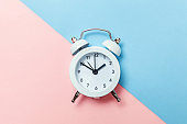 Vintage alarm clock Isolated on blue and pink pastel background