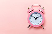 Vintage alarm clock Isolated on pink pastel background