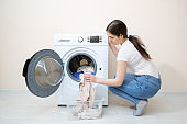 woman loads dirty clothes into washer near beige wall